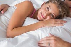Femme de sourire se trouvant sur le coffre de maris dans le lit Photographie stock libre de droits