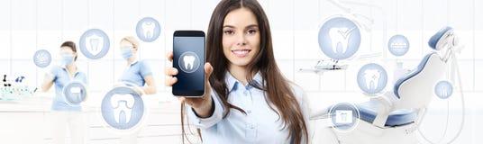 Femme de sourire de soins dentaires montrant le téléphone, les icônes de dents et le s futés photos stock