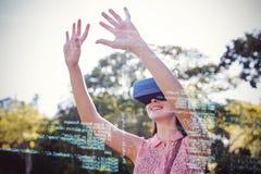 Femme de sourire soulevant ses mains tout en à l'aide d'un casque de VR 3d dans le parc Image libre de droits