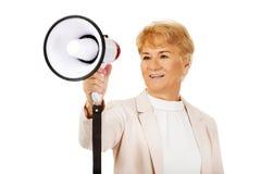 Femme de sourire supérieure criant par un mégaphone Photographie stock