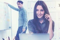 Femme de sourire sur le téléphone et un homme dans le bureau Images stock