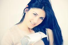 Femme de sourire tenant des cheveux avec le dessiccateur de coup image libre de droits