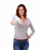 Femme de sourire tenant des dollars d'argent liquide tout en se tenant Images stock