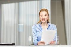 Femme de sourire tenant des papiers dans le bureau Image stock