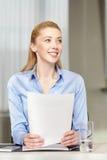 Femme de sourire tenant des papiers dans le bureau Photographie stock libre de droits
