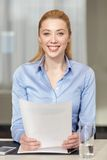 Femme de sourire tenant des papiers dans le bureau Photos libres de droits