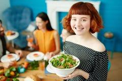 Femme de sourire tenant et tenant la salade dans la cuvette Photo stock