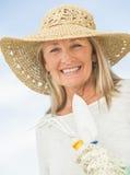 Femme de sourire tenant l'équipement de jardinage contre le ciel Photos libres de droits