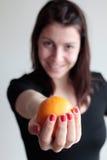 Femme de sourire tenant l'orange Images stock