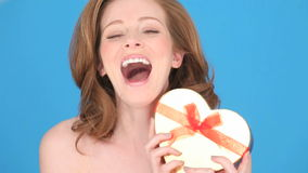 Femme de sourire tenant la boîte en forme de coeur Photographie stock