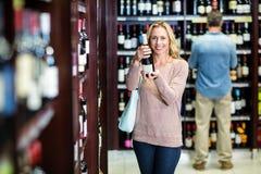 Femme de sourire tenant la bouteille de vin Photographie stock libre de droits
