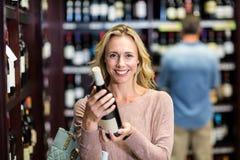 Femme de sourire tenant la bouteille de vin Photo stock