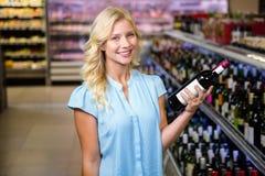 Femme de sourire tenant la bouteille de vin Images libres de droits