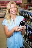 Femme de sourire tenant la bouteille de vin Photos stock