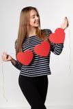 Femme de sourire tenant la guirlande de trois coeurs de papier rouges Photographie stock