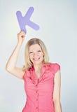 Femme de sourire tenant la lettre K photos libres de droits