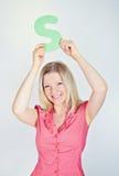 Femme de sourire tenant la lettre S photo stock