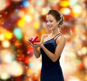 Femme de sourire tenant le boîte-cadeau rouge Images stock