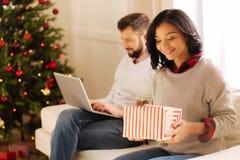 Femme de sourire tenant le boîte-cadeau tandis qu'homme travaillant sur l'ordinateur portable Photo stock