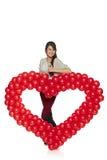 Femme de sourire tenant le coeur rouge de ballon Image stock