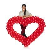 Femme de sourire tenant le coeur rouge de ballon Images stock