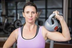 Femme de sourire tenant le kettlebell lourd Image libre de droits