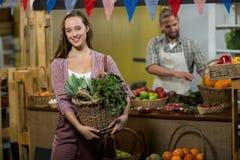 Femme de sourire tenant le panier des légumes verts dans l'épicerie Image stock