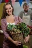Femme de sourire tenant le panier des légumes verts dans l'épicerie Image libre de droits