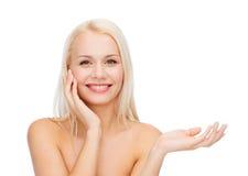 Femme de sourire tenant le pot imaginaire de lotion photo stock