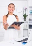 Femme de sourire tenant le presse-papiers dans le bureau de société à l'intérieur Photo stock