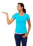 Femme de sourire tenant le produit invisible Image libre de droits