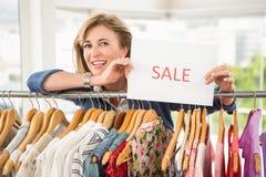 Femme de sourire tenant le signe de vente Photographie stock libre de droits