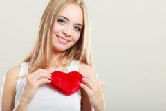 Femme de sourire tenant le symbole rouge d'amour de coeur Photographie stock