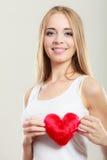 Femme de sourire tenant le symbole rouge d'amour de coeur Images stock