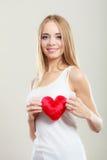 Femme de sourire tenant le symbole rouge d'amour de coeur Photographie stock libre de droits