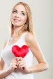Femme de sourire tenant le symbole rouge d'amour de coeur Images libres de droits