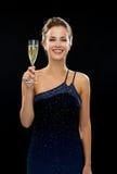 Femme de sourire tenant le verre de vin mousseux Image libre de droits