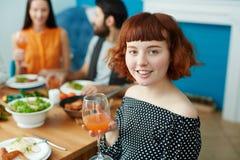 Femme de sourire tenant le verre tout en mangeant avec des amis Photos libres de droits
