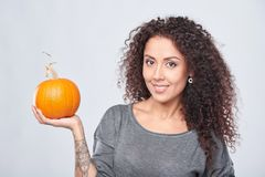 Femme de sourire tenant les potirons mûrs photo stock