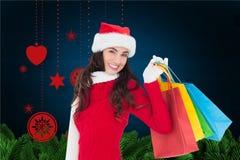 Femme de sourire tenant ses paniers sur le fond digitalement produit de Noël images stock