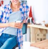 Femme de sourire tenant son téléphone portable dans la cuisine Photos libres de droits