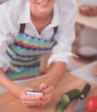 Femme de sourire tenant son téléphone portable dans la cuisine Photos stock