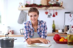 Femme de sourire tenant son téléphone portable dans la cuisine Femme de sourire Image libre de droits