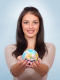 Femme de sourire tenant un globe Photos stock