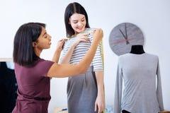 Femme de sourire tenant une bande de mesure tout en aidant son tailleur Photographie stock libre de droits