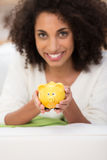 Femme de sourire tenant une tirelire jaune Photographie stock libre de droits