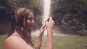 Femme de sourire tirant la photo panoramique de la cascade tropicale au téléphone portable dans faire de déplacement de blogger d clips vidéos