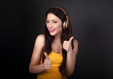 Femme de sourire toothy heureuse écoutant l'écouteur de radio de musique image stock