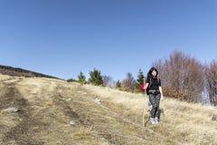 Femme de sourire trimardant dans une haute montagne Photo stock