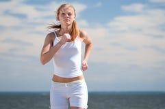 Femme de sport exécutant sur la plage Image stock